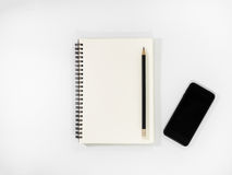 Black pencil above an open notebook. Black pencil above an open notebook with black smartphone on white background royalty free stock photo