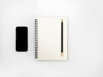 Black pencil above an open notebook. Black pencil above an open notebook with black smartphone on white background Royalty Free Stock Image