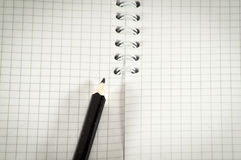 Black pencil on a background of the disclosed notepad. Royalty Free Stock Photo