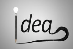 Black pencil with a bright light bulb idea word written Royalty Free Stock Photo