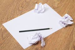 Black pencil on clear white paper with crumble paper balls on wo Stock Photos
