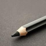Black pencil on dark surface Royalty Free Stock Images