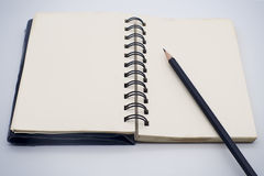 Black pencil on open white paper note book Stock Photography