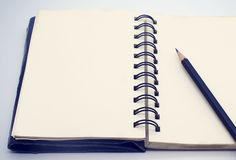 Black pencil on open white paper note book Royalty Free Stock Photo