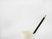 Black pencil in paper cup. Black pencil in paper cup on white background Stock Image