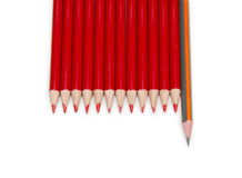 Black pencil standing out from the red pencils, isolated Stock Images
