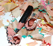 Black pencil use up. Small black pencil on motley sawdust Royalty Free Stock Images