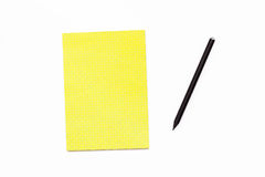 Black pencil and a yellow Notepad on a white background. Minimal business concept office Desk. Stock Image