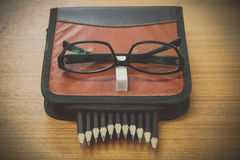 black pencils in a bag and glasses  on brown wood Stock Photo