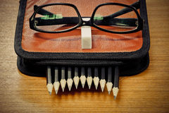 black pencils in a bag and glasses  on brown Stock Photography
