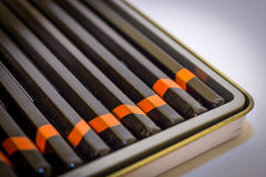 Black pencils with orange stripes in metal box.  royalty free stock images