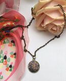 Black pendant with a rose flower. And a pink scarf Royalty Free Stock Images