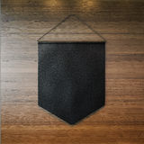 Black pennant hanging on the wall at wooden Royalty Free Stock Photography