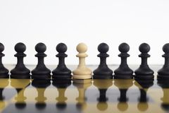 Black peons aligned where one is white. It shows the uniqueness royalty free stock image