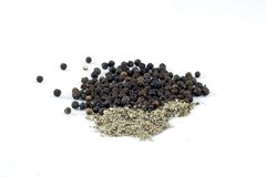 Black pepper. Whole and cracked black pepper Stock Image