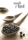Black pepper. Wooden spoon, table royalty free stock photos