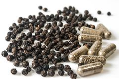 Black pepper and Capsules. Royalty Free Stock Photography