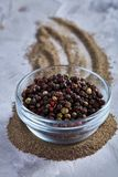 Black pepper corns in glass bowl with clipping path on white background, top view, selective focus, vertical. Some copy space for your inscription. Natural Stock Photography