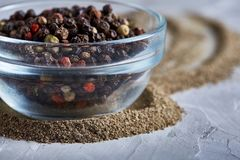 Black pepper corns in glass bowl with clipping path on white background, top view, selective focus, vertical. Some copy space for your inscription. Natural Royalty Free Stock Photos