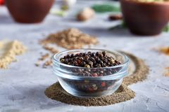 Black pepper corns in glass bowl with clipping path on white background, top view, selective focus, vertical. Some copy space for your inscription. Natural Stock Photo