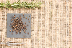 Black pepper on dark plates with rosemary and antique fork. Black peppercorns on dark plate with rosemary and antique fork. Rustic background. Warm color. With Stock Images