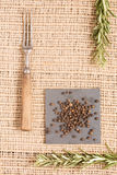 Black pepper on dark plates with rosemary and antique fork. Black peppercorns on dark plate with rosemary and antique fork. Rustic background. Warm color Stock Photo