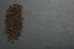 Black pepper on dark stone background royalty free stock images