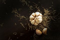 Black pepper, Garlic and rosemary on wooden plate on black backg royalty free stock photography