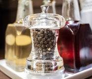 Black pepper in glass grinder container Stock Image