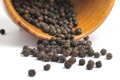 Black pepper grains into a bowl Royalty Free Stock Images