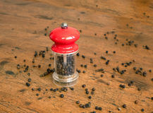 Black pepper and manual mill on wooden background Royalty Free Stock Image
