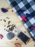 Black pepper. Organic black peppercorns in glass jar on wooden table Stock Photo