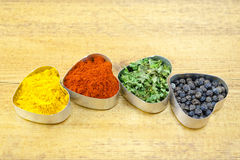 Black pepper, paprika, curry and basil Stock Photography