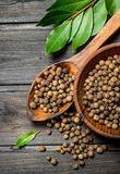 Black pepper peas in bowl with spoon and Bay leaves stock photo