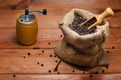 Black pepper peas in a sack and pepper mill on a wooden table Royalty Free Stock Images