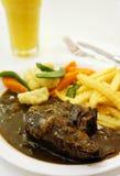 Black pepper rib eye steak with orange juice. On white background Stock Photo