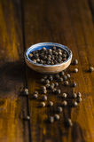 Black pepper in a  rustic bowl. Black pepper in a rustic board and spilled on a wooden table Stock Images