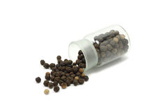 Black pepper seeds in a glass bottle. On a white background Royalty Free Stock Photo