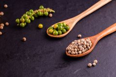 Black pepper spice peppercorn on wooden spoon and dark rustic background stock images