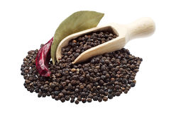 Black pepper in spoon and bay leaf Stock Photos
