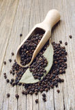 Black pepper in spoon and bay leaf Stock Images