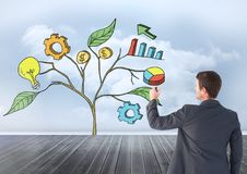 Man holding pen and Drawing of Business graphics on plant branches on wall Stock Photo