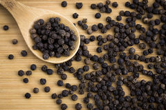 Black pepper. On the wood background Royalty Free Stock Images
