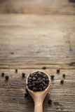 Black pepper on wooden background Royalty Free Stock Images