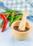Black pepper in wooden bowl and chili pepper Royalty Free Stock Photo