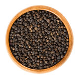 Black pepper in wooden bowl over white Royalty Free Stock Photo