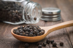 Black pepper on wooden spoon royalty free stock photography