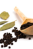 Black pepper on wooden spoon and bay leaves Stock Photos