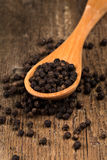 Black pepper on wooden spoon. And wood background Stock Photography