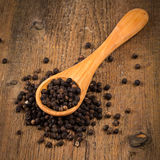 Black pepper on wooden spoon. And wood background Royalty Free Stock Photos